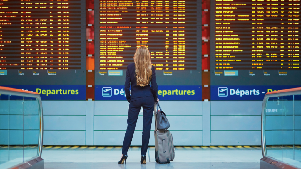 Airport-woman-standing-in-front-of-flight-board-Coronavirus