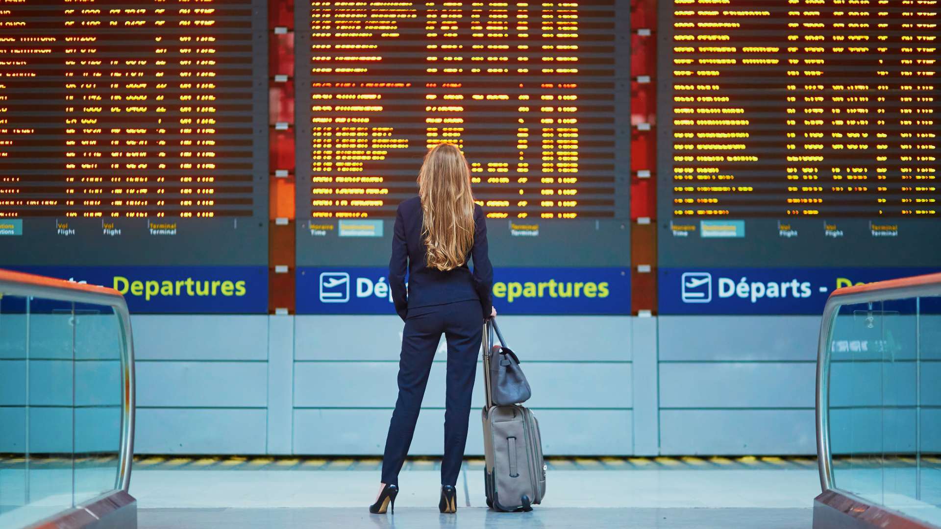 Airport-woman-standing-in-front-of-flight-board