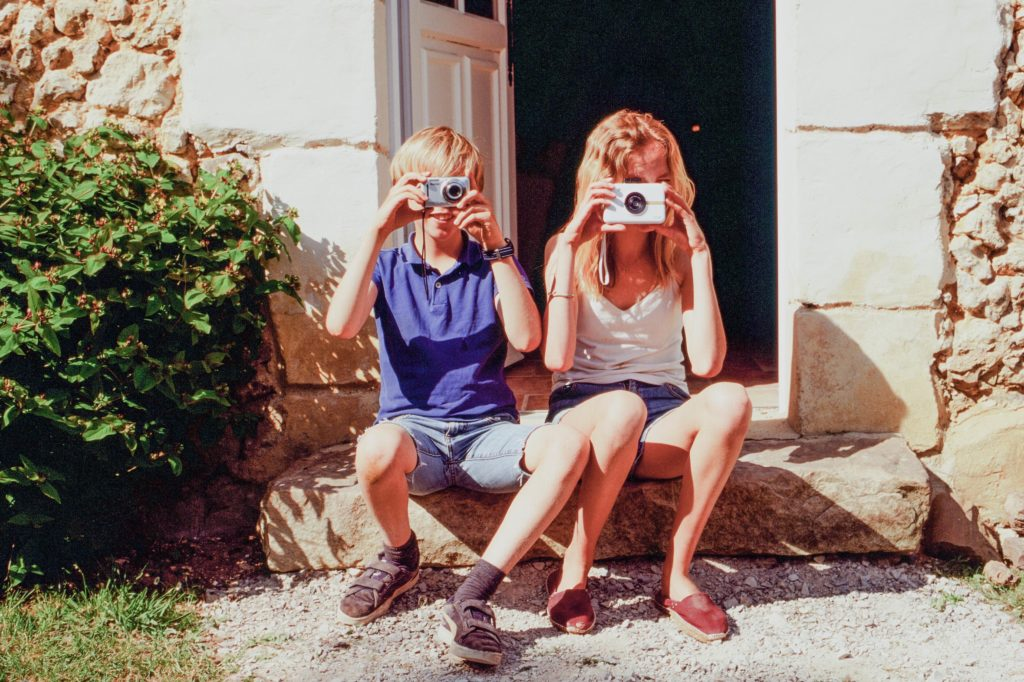 two-kids-pointing-cameras-at-the-photo-taker